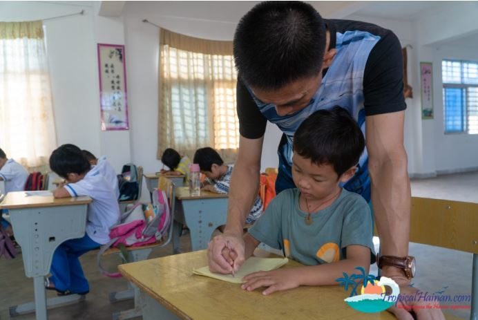 A teacher in Hainan helping one of his students in Beigang elementary school