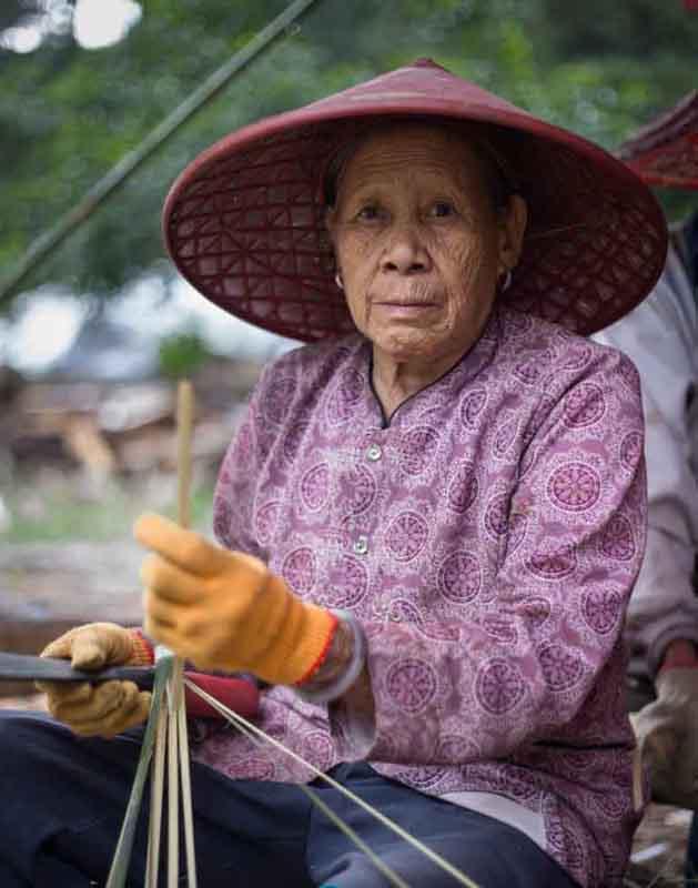 A Li Minority Villager Working on House Building